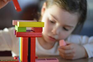 Young girl explores scientific thinking as she builds with blocks