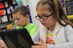 Young students explore STEM using a tablet to complete their lesson