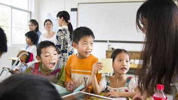 3 elementary students listen closely to their teacher